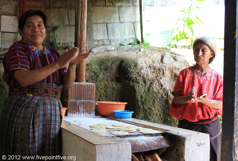 Women make tortillas on a wood fire oven